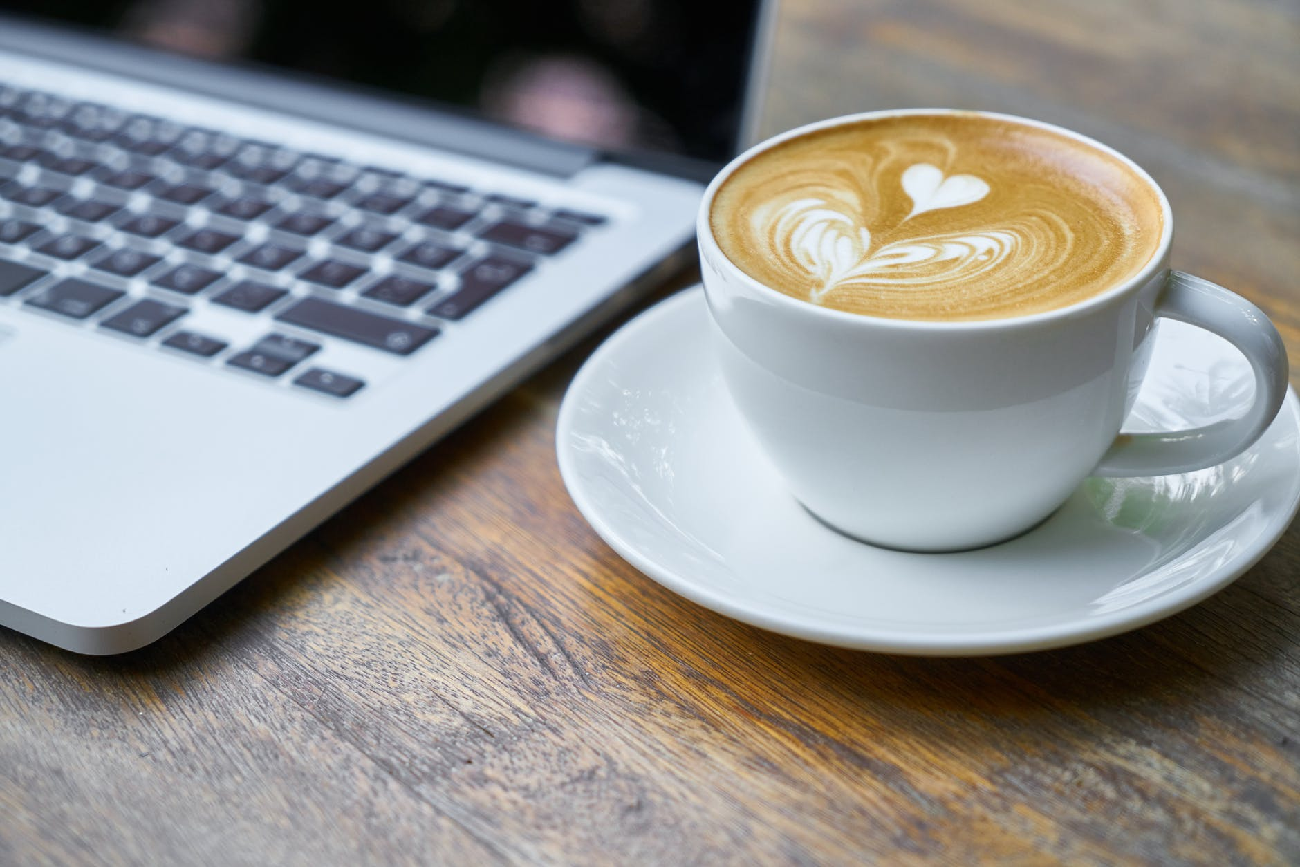 Fancy coffee in a cup and saucer on a wooden table next to a laptop.